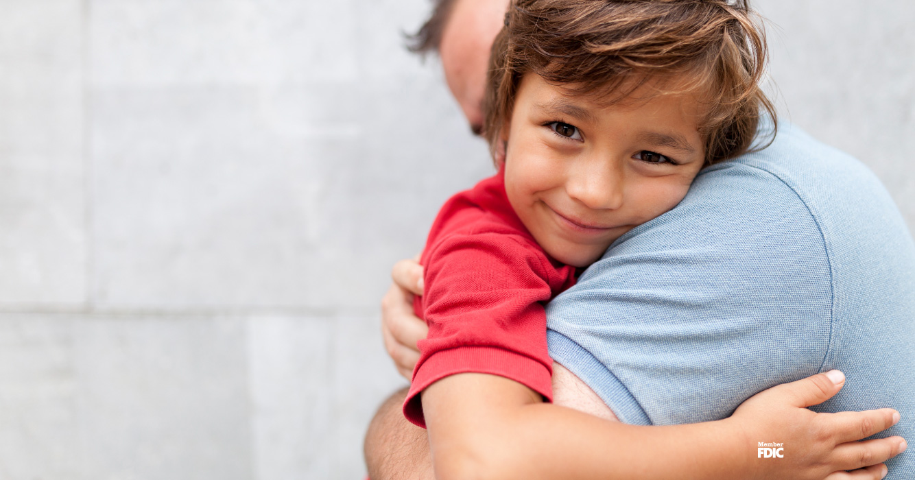 Young boy smiles as he hugs his father.