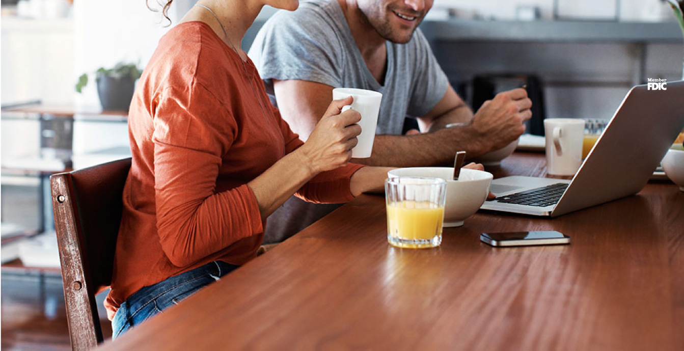 Young couple looking at a laptop while they enjoy their breakfast at home.
